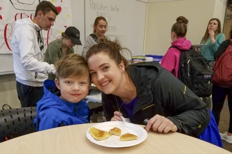 Brittany Goff, the adviser for the (Miss)ter Union Pageant, poses with her son Henry as they took advantage of the pancakes made by contestant Kaitlyn Milliken. The months-long event raises funds for charity. The pageant itself is Saturday at Union High School. Photo by Paul Valencia