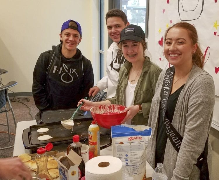 Kaitlyn Milliken, right, one of 15 contestants this year for (Miss)ter Union. However, it really is a school-wide event, a large group effort for this charity fundraiser. Senior Gabe Rodgers, left, was a contestant last year. And sophomores Lucas Horowitz and Katie Boda, helped Milliken with her pancake drive Thursday morning. Photo by Paul Valencia