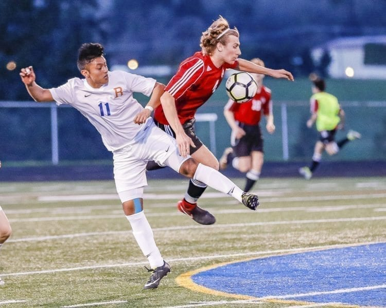 Camas' Jake Fuller (4) and Ridgefield's Carlos Cruz (11) battle for position as they battle for the ball Monday at Ridgefield High School. Camas won the non-league match 3-1. Photo by Mike Schultz