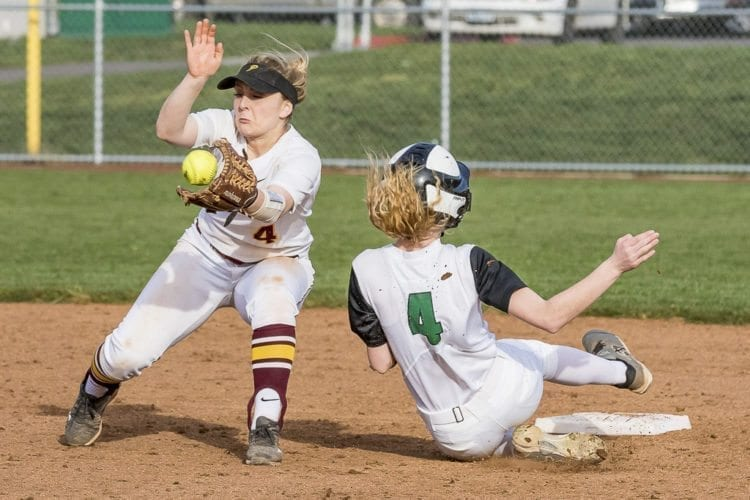Woodland's Kat Paloutzian slides in safely in front of Prairie's Carley Wentworth during their non-league game Monday. Woodland beat Prairie 4-0. Photo by Mike Schultz