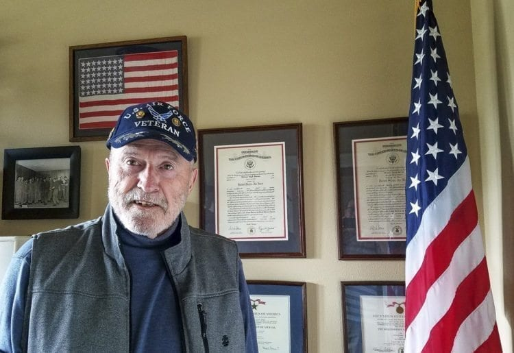 Michael Burton stands in front of many of his memories from his days as an officer in the U.S. Air Force. The Vietnam veteran went nearly 40 years before getting help for posttraumatic stress disorder. Now, it it is his mission in life to help other veterans, reminding them it is never too late. Photo by Paul Valencia