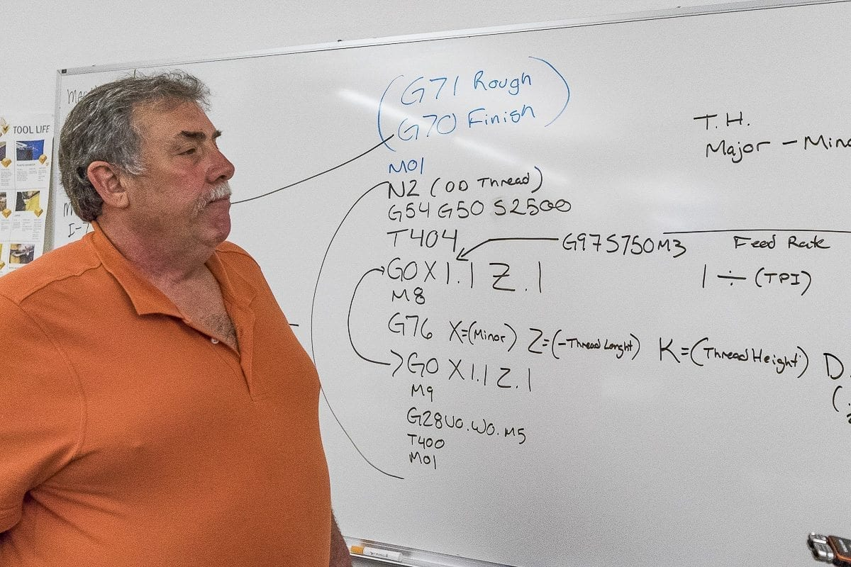 Instructor Bruce Wells shows off a mathematical formula for fabrication machines in Clark College's machining shop. Photo by Mike Schultz