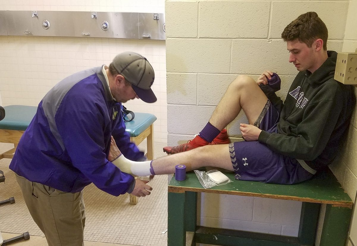 Heritage athletic trainer Andy Goss takes care of soccer player Spencer Clark. Goss, who has been at Heritage for six years, will be recognized this week at the state athletic directors conference as the top athletic trainer in Washington. Photo by Paul Valencia