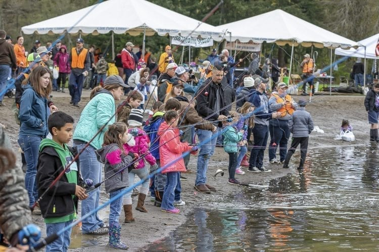 Children, adults and volunteers stand along the beach at Klineline Pond in Salmon Creek Park Saturday morning for the Klineline Kids Fishing Derby. Photo by Mike Schultz