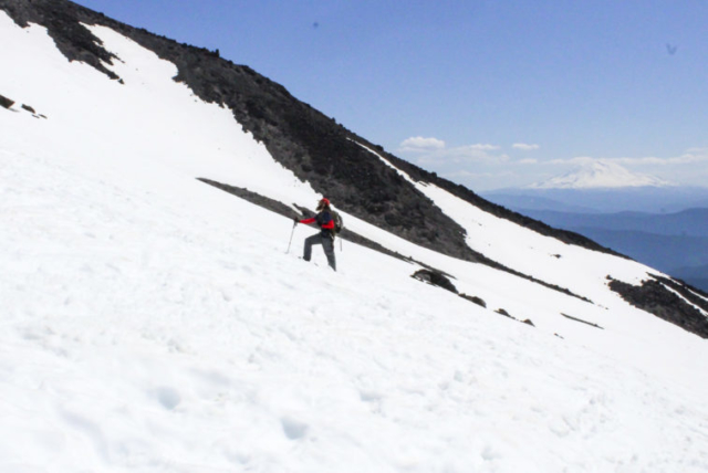 A climber looks toward the summit as Mount Adams looms in the background. Photo by Eric Schwartz