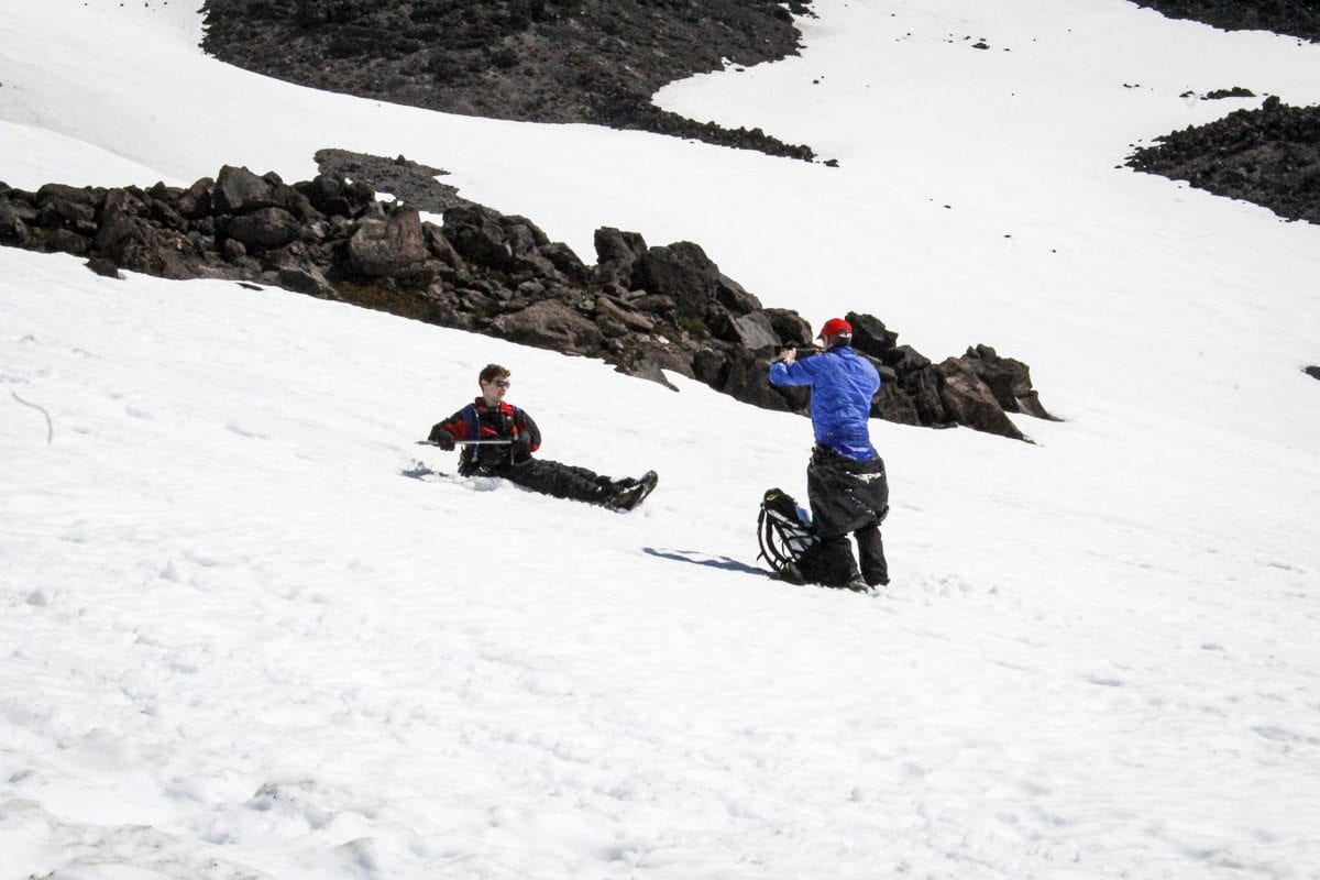 A man photographs a friend glissading down the slopes of Mount St. Helens. Photo by Eric Schwartz