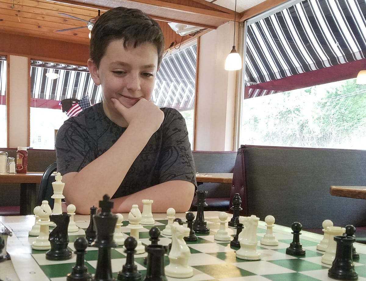 """Christian Stupak, an 11-year-old who attends Woodburn Elementary School in Camas, likes to challenge himself with taking advanced math and learning how to play chess. He recently earned """"High Honors"""" after testing by Johns Hopkins Center for Talented Youth. Photo by Paul Valencia"""