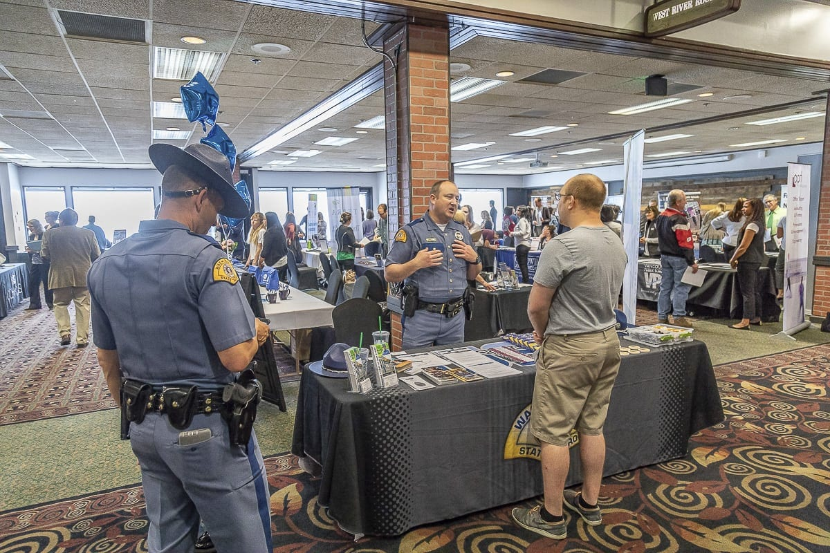 Washington State Patrol recruiters speak with an attendee of the Jobs Fair at Warehouse 23 in Vancouver Tuesday morning. Photo by Mike Schultz