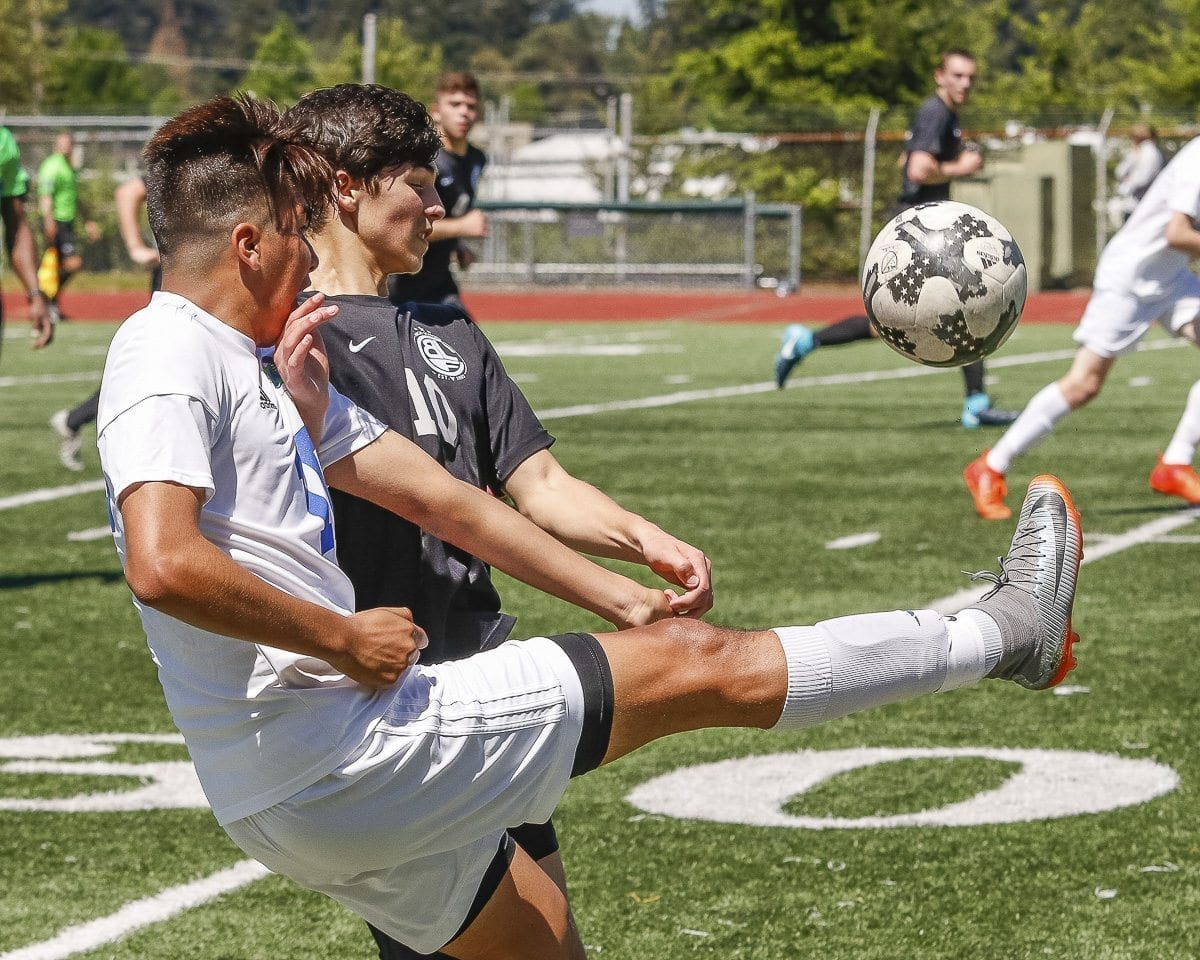 Joaquin Hernandez of Mountain View (white jersey) battles with a Bonney Lake player for control of the ball during their Saturday elimination match. Mountain View would go on to win 1-0 in overtime to make it to state. Photo by Mike Schultz