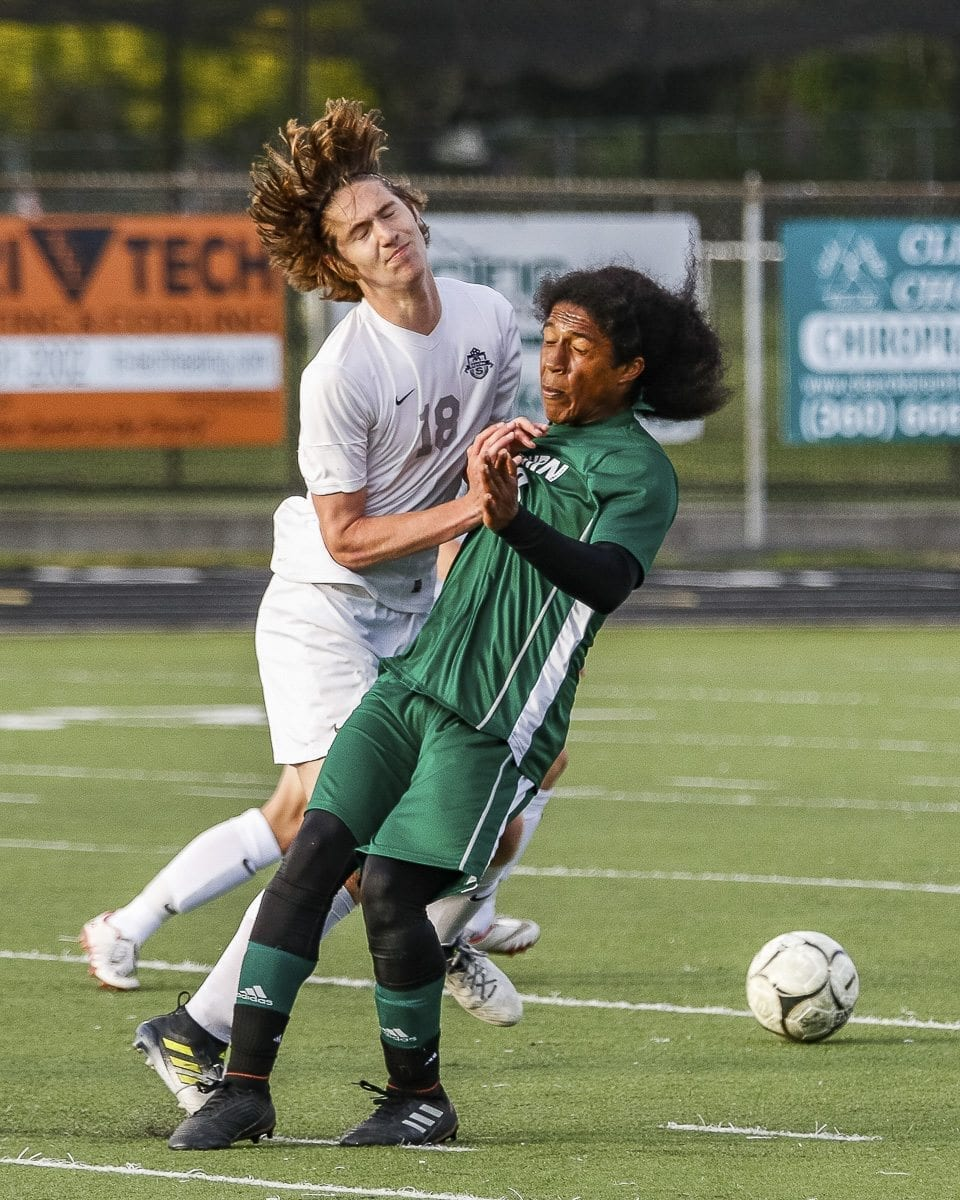 Mountain View's Nicholas Roddy (18) battles with a Auburn defender for possession of the ball during Wednesday's playoff soccer game. Photo by Mike Schultz