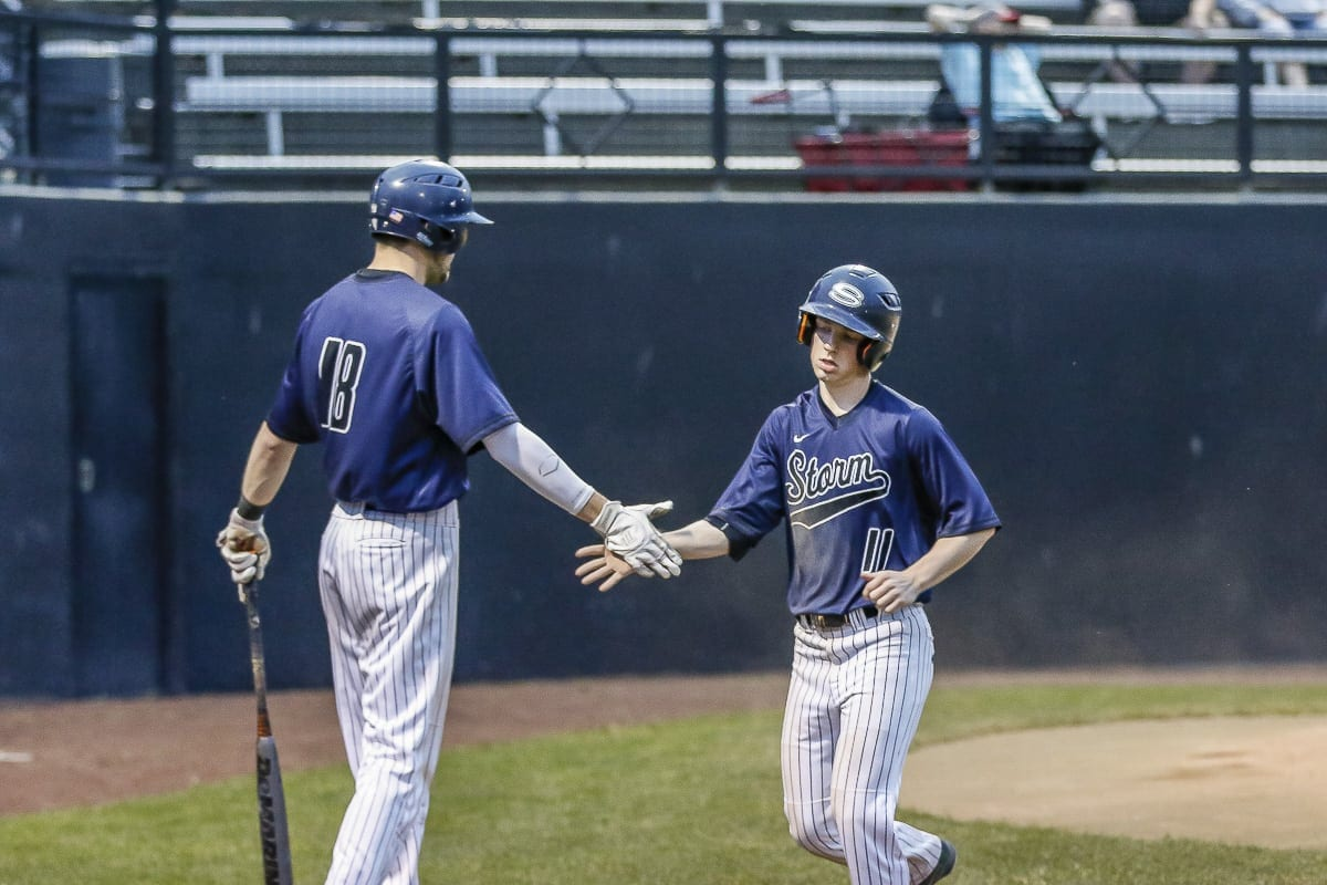 Skyview players Daniel Copeland (18) and Brent Monahan (11) slap hands during a playoff game earlier this month. The Storm are headed to the semifinals of the Class 4A state baseball tournament this weekend. Photo by Mike Schultz