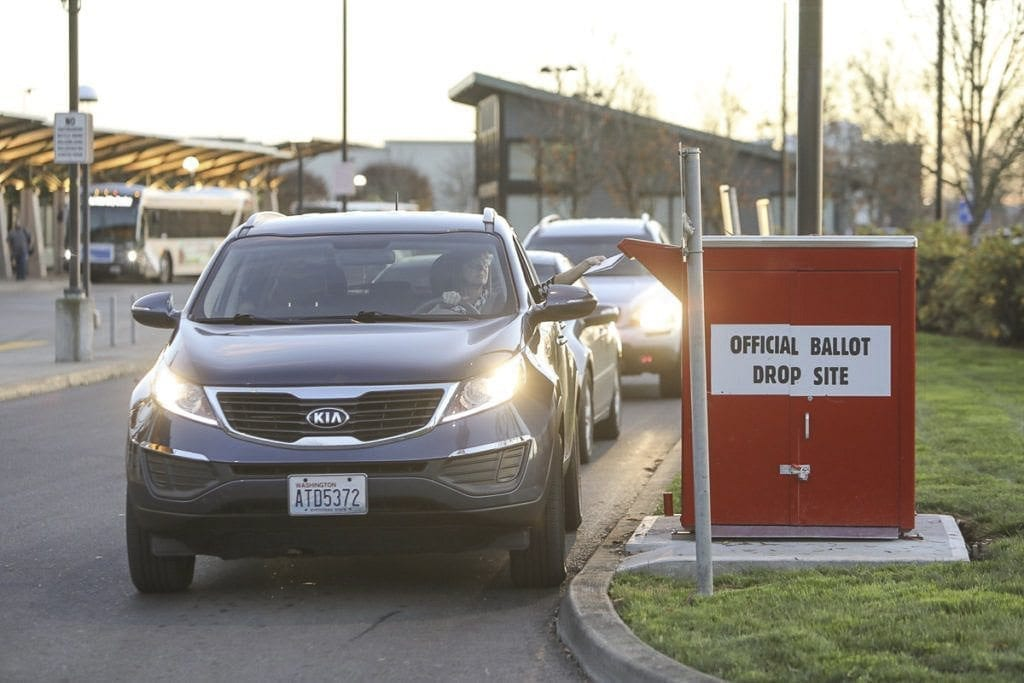 Voters submit their ballots at a drive-through dropbox in this 2016 file photo. Photo by Mike Schultz