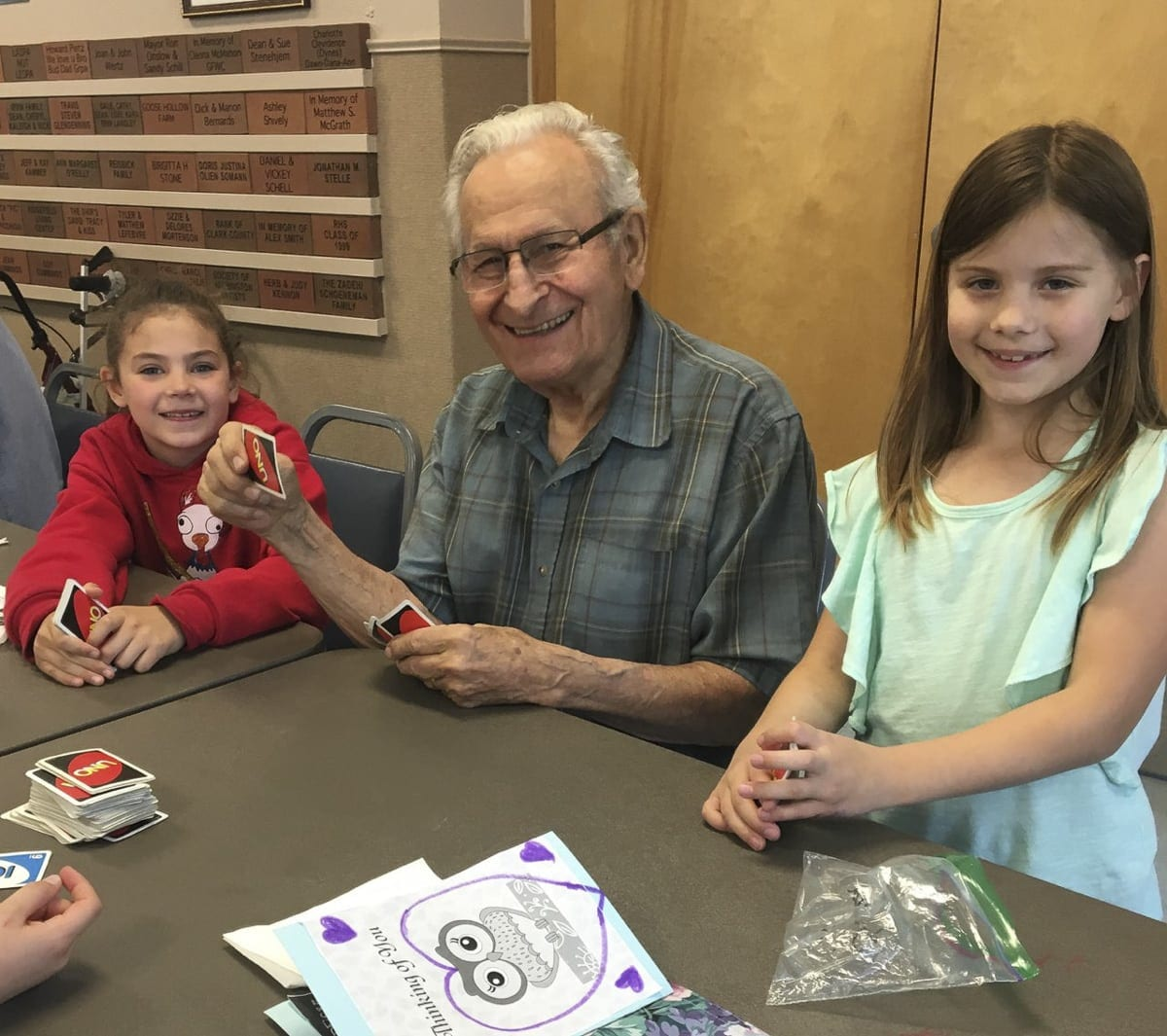 Union Ridge Elementary School second graders Lizzy Bloom (at left) and Clara Bruguier play cards with Ken Carson at Ridgefield's Community Center. Photo courtesy of Ridgefield School District