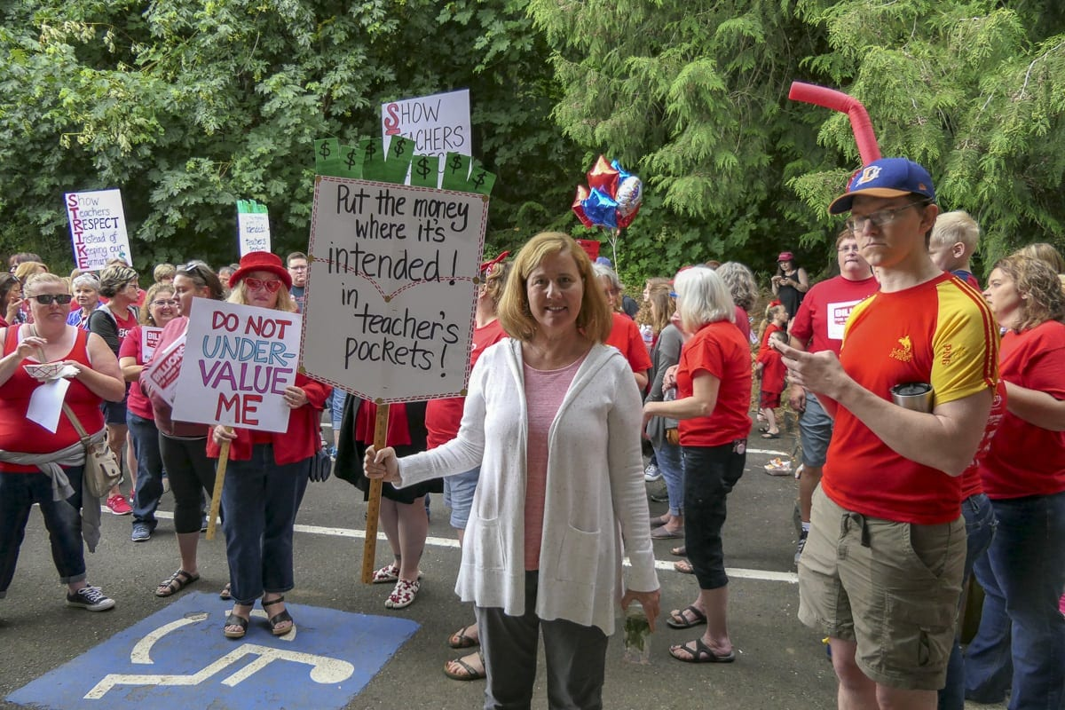 Battle Ground parent Jodie Housley holds her sign at a rally outside Battle Ground School District headquarters in support of higher pay for teachers. Photo by Chris Brown