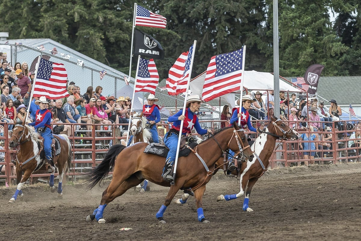 Riders and horses open Thursday's performance of the Vancouver Rodeo during the Grand Entry. The rodeo, at the Clark County Saddle Club, is likely having its final run at its current location. The property likely will be sold and the rodeo is to be moved. Photo by Mike Schultz
