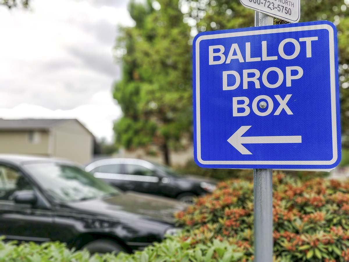 A sign points to a ballot drop box location near the City of Battle Ground building. Photo by Chris Brown