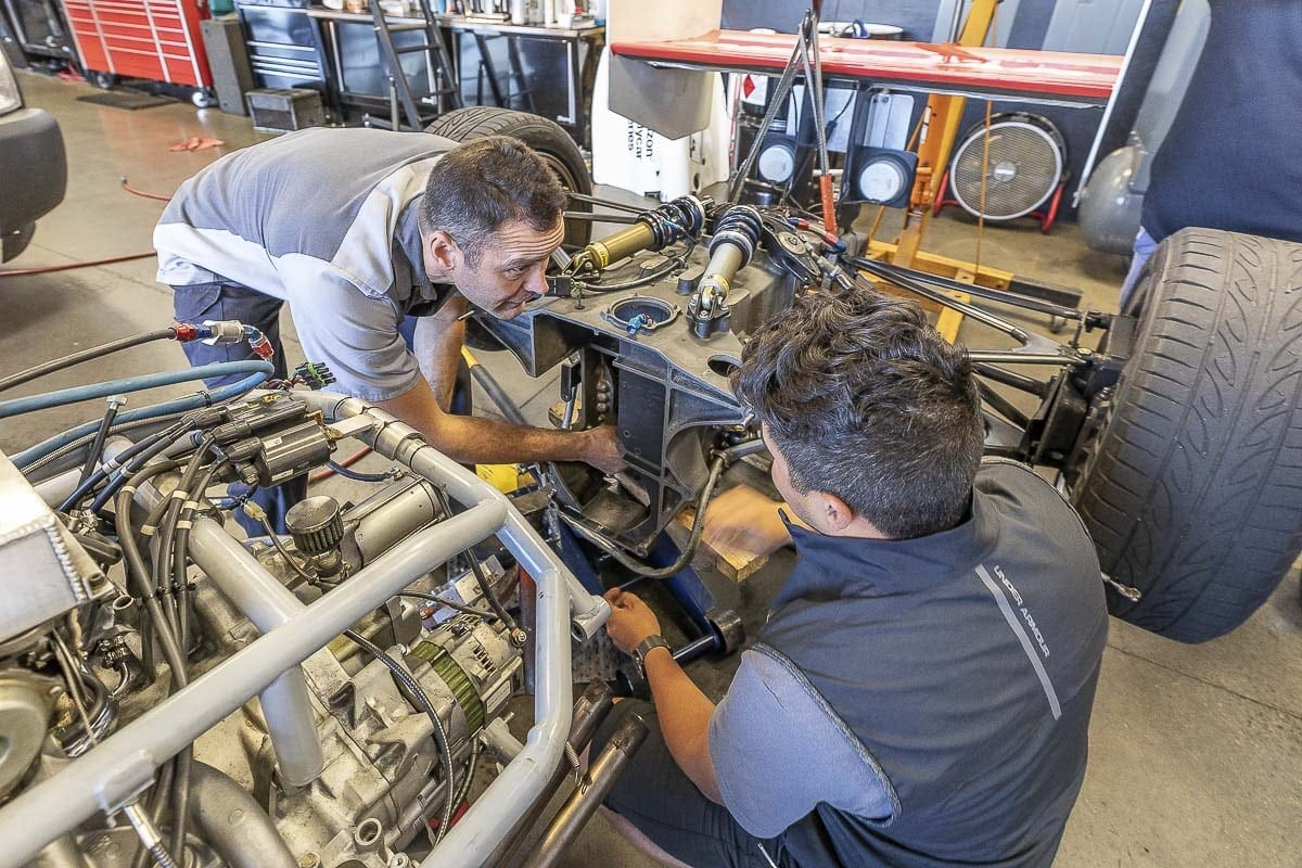 Gaynors Automotive technician Pat Clark (left) consults with Isaac Sanchez (right), of IndyCar Experience, on the needed repairs to a promotional car for this weekend's Grand Prix of Portland. Photo by Mike Schultz