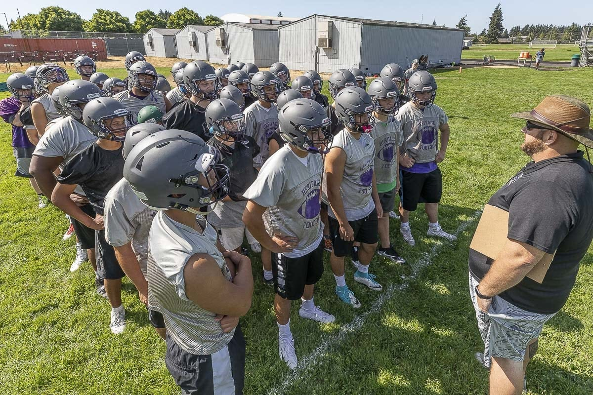 Heritage football coach Matt Gracey addresses a group of his players at a recent practice. Photo by Mike Schultz