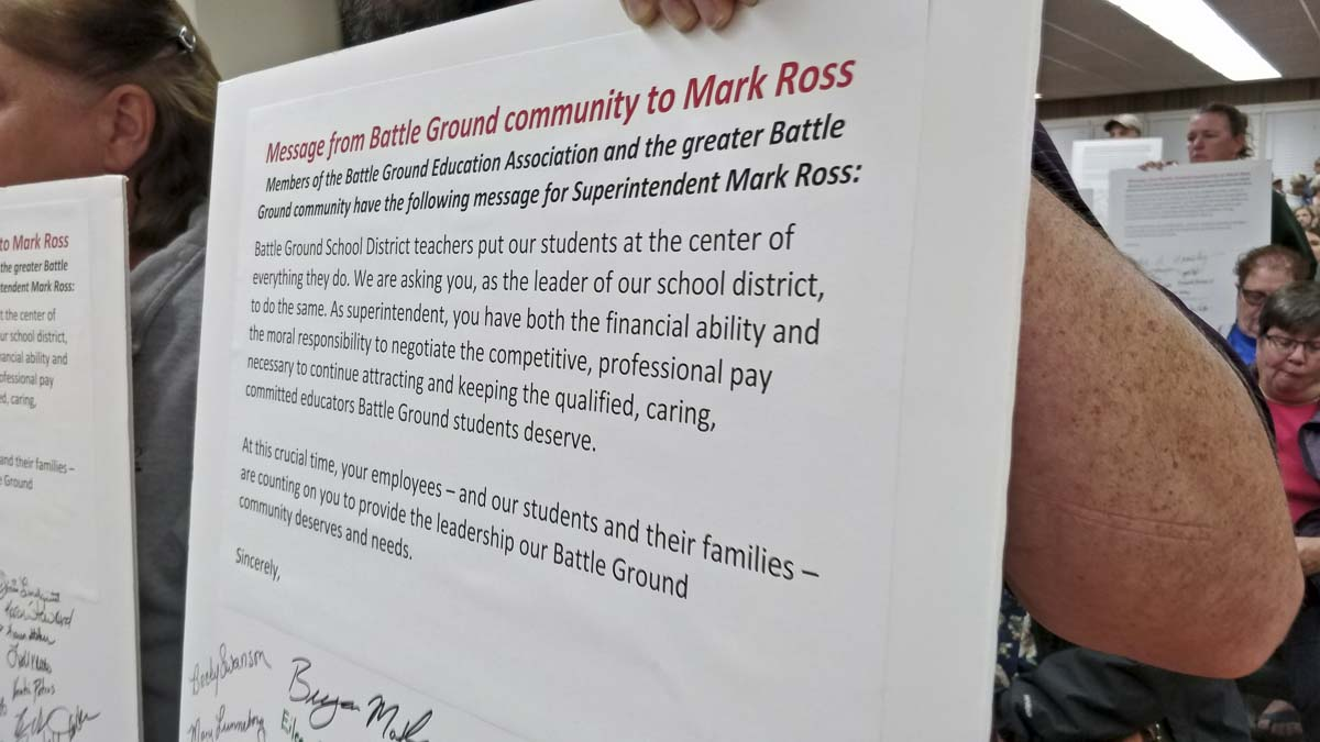 Community members held signed boards with a statement for Superintendent Mark Ross during Wednesday's special meeting of the Battle Ground School Board. Photo by Chris Brown