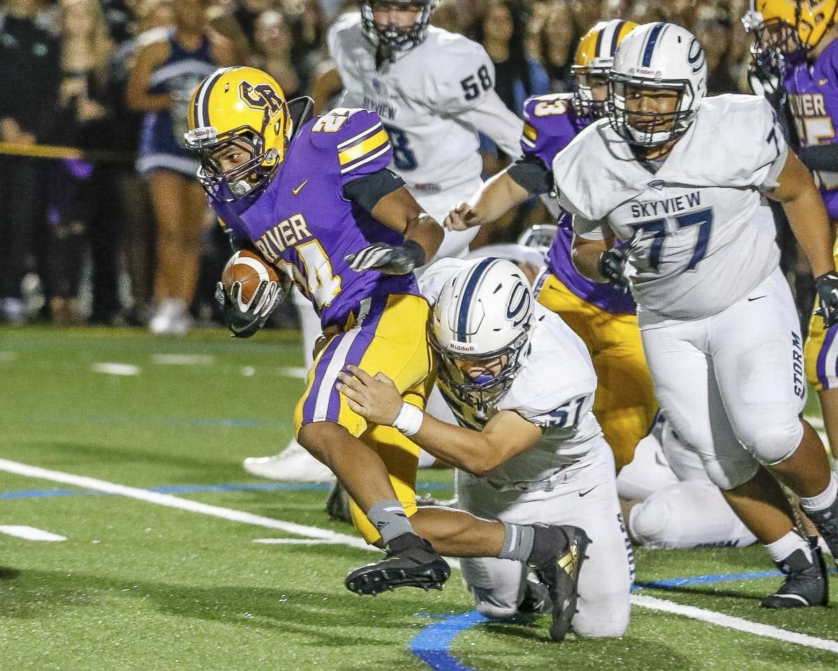 Columbia River's Isaac Bibb-O'Neil (24) attempts to elude a pair of Skyview defenders in Friday night's non-league game at Columbia River High School.