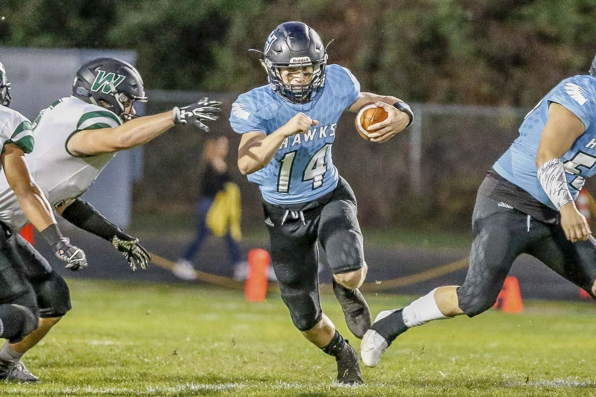 Hockinson quarterback Levi Crum (14) had four touchdown passes and scored on a touchdown run in the Hawks' 42-27 win over Woodland Friday at Hockinson High School. Photo by Mike Schultz