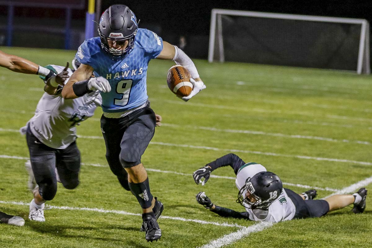 Hockinson receiver Peyton Brammer (9) eludes Woodland defenders and avoids the sideline during the Hawks' 42-27 win Friday at Hockinson High School. Photo by Mike Schultz
