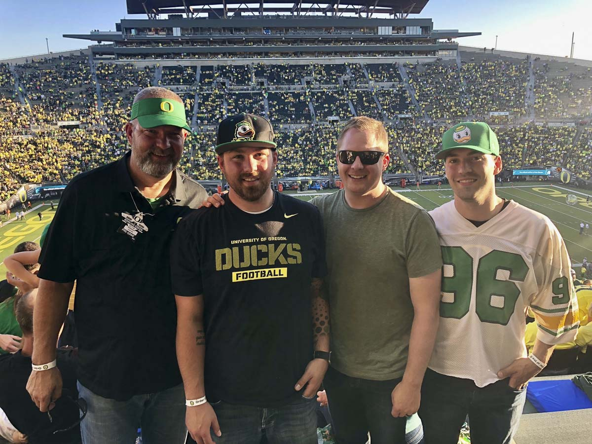 Mike Kesler, left, hangs out with his sons Ryan, Brandon, and Shane at least week's Oregon Duck football game. Kesler, the head coach at Battle Ground, played for the Ducks in 1978 and 1979. He was an honorary captain last week in Eugene. Photo courtesy of Mike Kesler