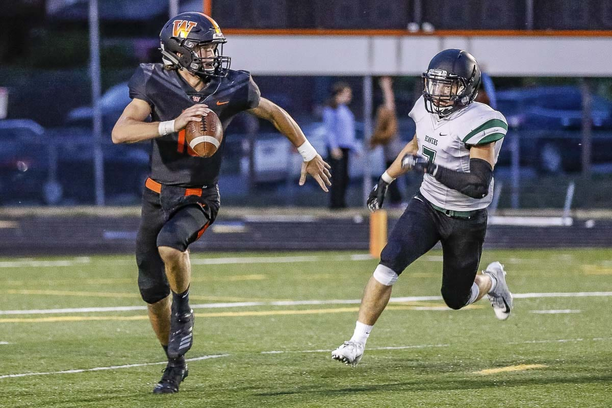 Washougal quarterback Dalton Payne (10) attempts to outrun Woodland defender Reid Hope (7) during Friday's Class 2A Greater St. Helens League game at Washougal High School. Photo by Mike Schultz