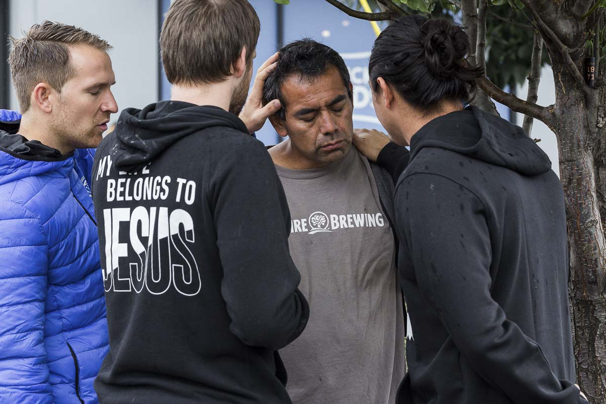Luke Donald, (center), youth pastor from The Promise Church in Woodland, prays for a man to be healed on the streets of Portland. He is joined by Rudi Pino, (left), of The Church of Truth, and Willy Menendez, (right), pastor at True Life Church, both in Vancouver. Photo Courtesy of Compassion to Action & Avel Isupov
