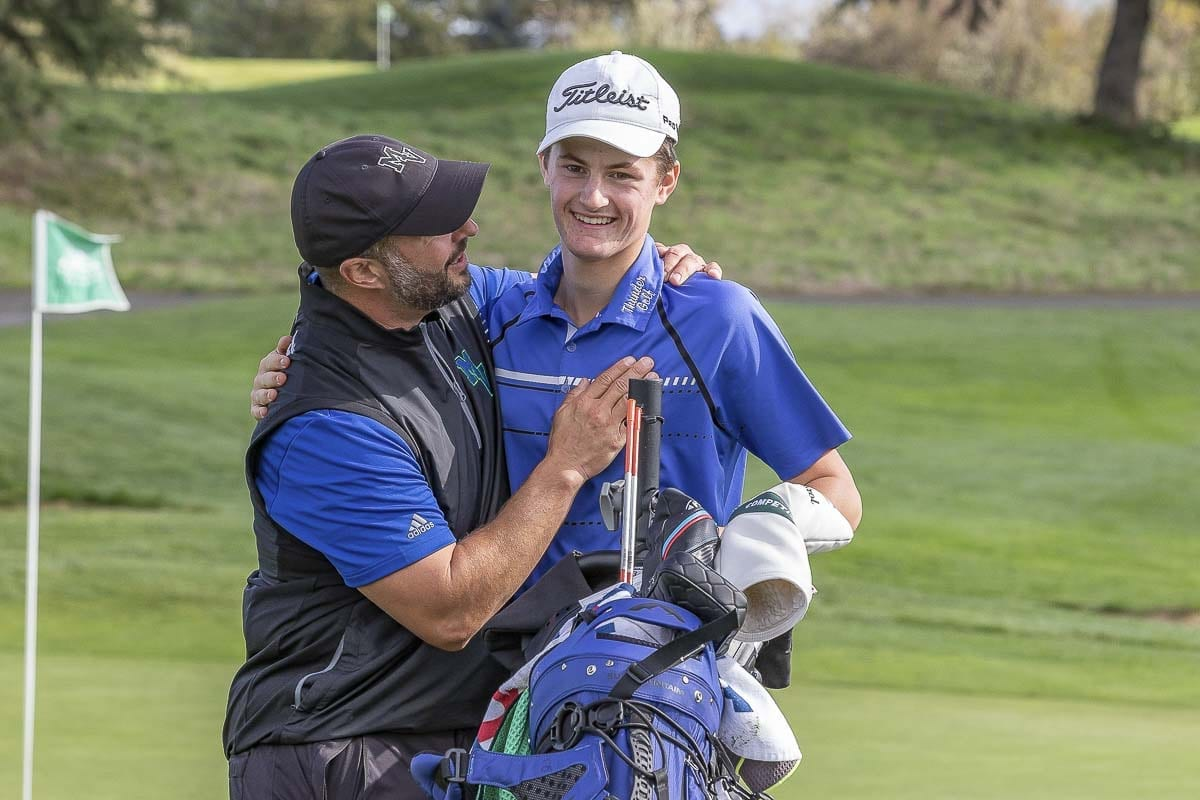 Graham Moody is all smiles as he gets congratulated by Mountain View golf coach James Petersen after the round Tuesday. Moody, a sophomore, won the Class 3A District 4 boys golf tournament at Tri-Mountain Golf Course. Photo by Mike Schultz