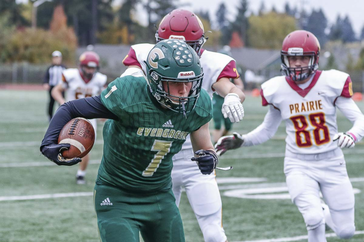 Evergreen running back Gideon Macabeo (7) attempts to run away from a pair of Prairie defenders, including Sam Salzman (88). Photo by Mike Schultz