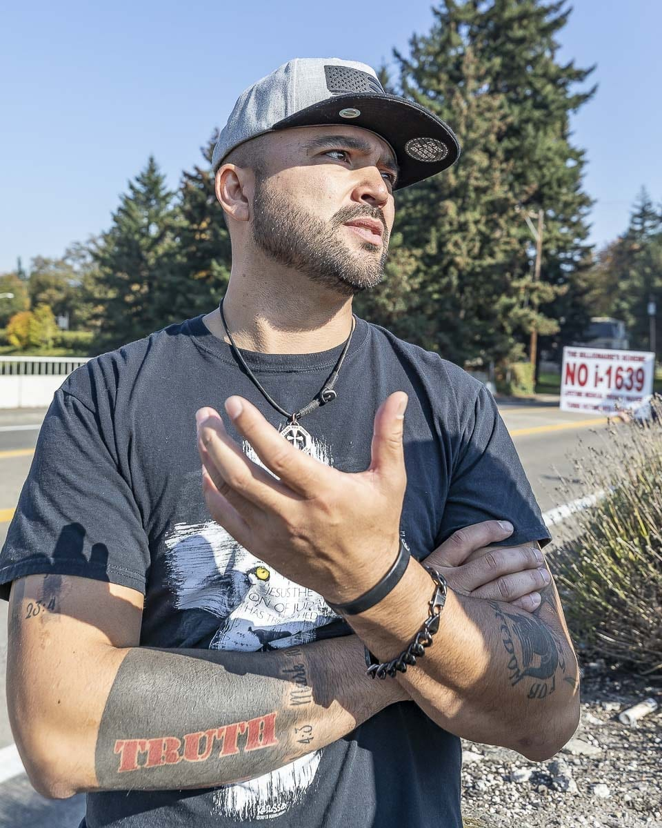 Joey Gibson, founder of Patriot Prayer, talks with reporters while his group demonstrates atop the Evergreen Boulevard overpass in Vancouver. Photo by Mike Schultz