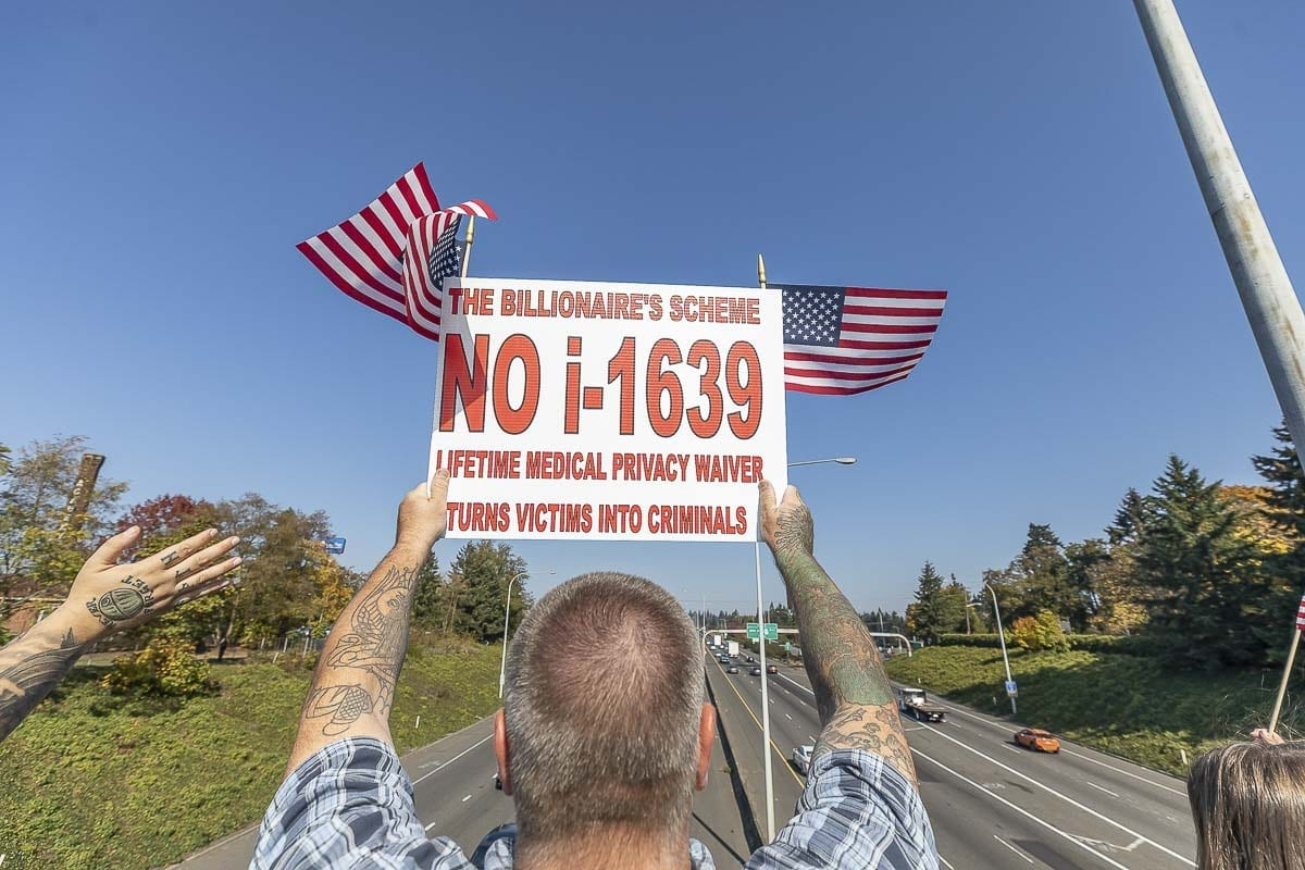 Nick Gibson, of Camas, holds a sign in opposition of Initiative 1639 atop the Evergreen Boulevard overpass in Vancouver. I-1639 would increase background checks for firearm purchases, as well as raise the age to buy semi-automatic rifles from 18 to 21. Photo by Mike Schultz
