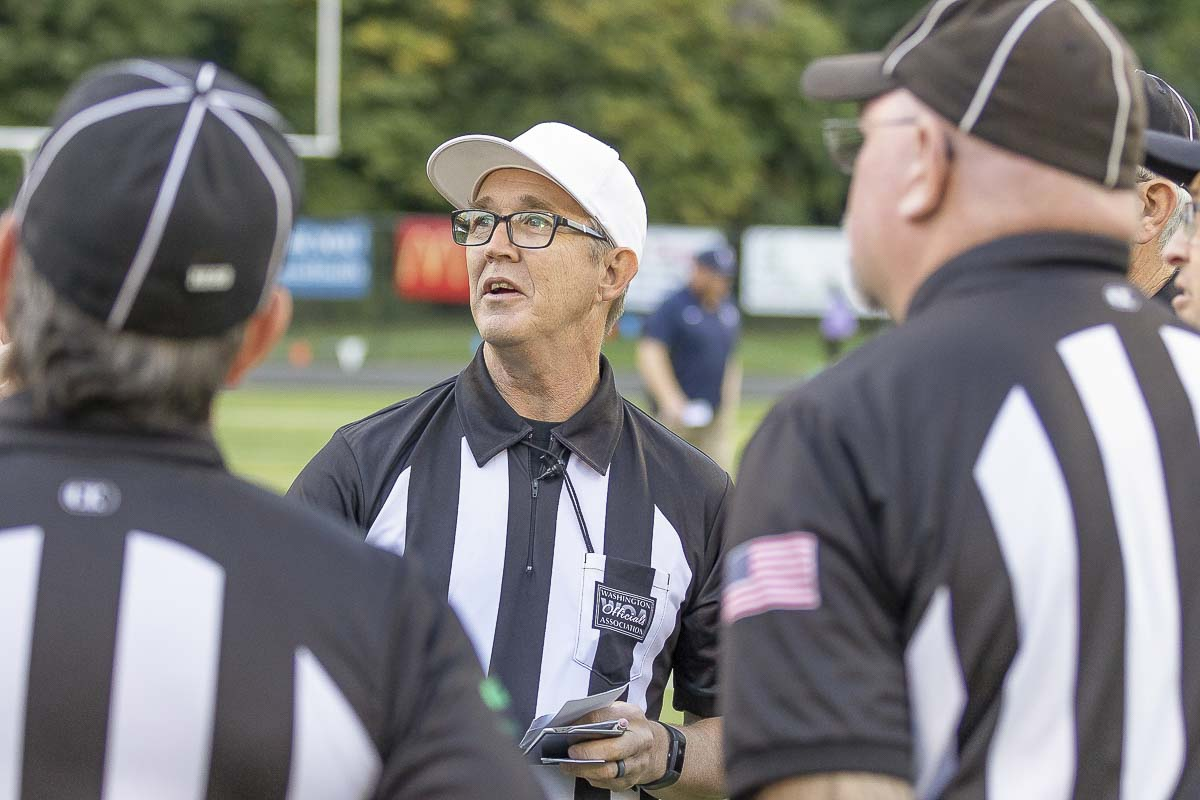 Referee Jim Goss talks to his crew prior to a recent game at Kiggins Bowl. Goss has been an official for more than 30 years. Photo by Mike Schultz