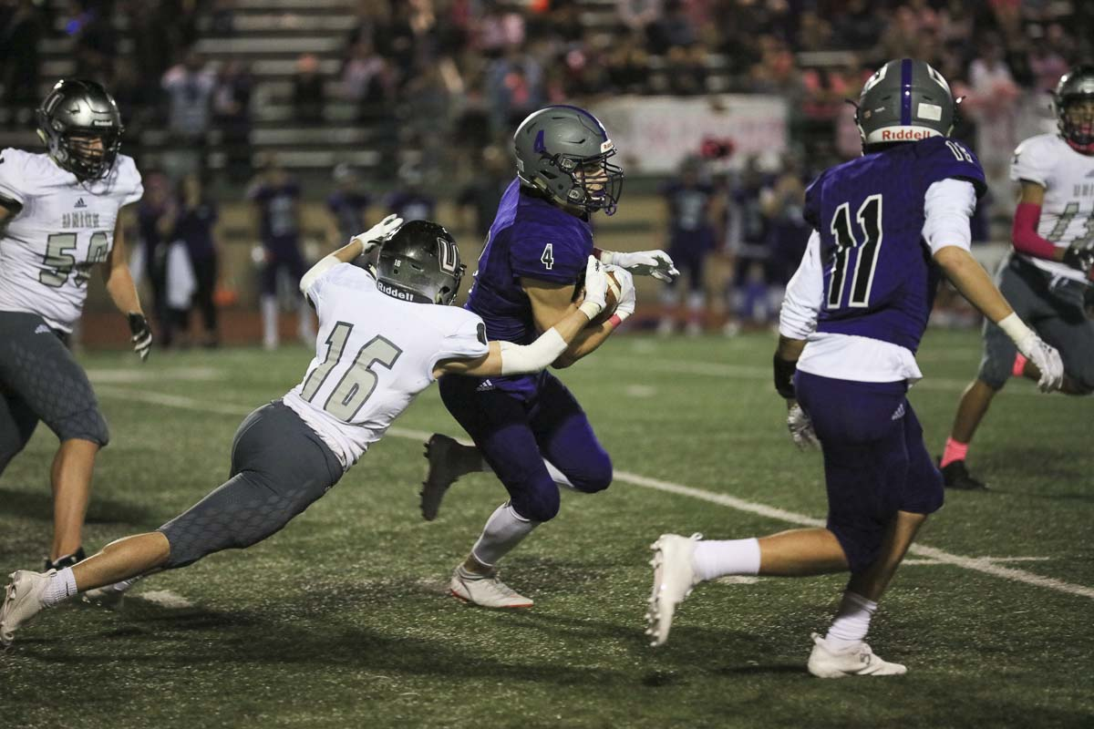 Michael Rogers (16) of Union tries to bring down Daniel Barrera (4) of Heritage during Thursday's game at McKenzie Stadium. Union got the shutout, beating Heritage 34-0 to improve to 7-0 this season. Photo courtesy of Heather Tianen