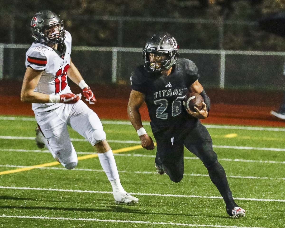Union running back Jojo Siofele (26) rushes around the end during Friday's win over Camas at McKenzie Stadium. Siofele rushed for one of the Titans' two touchdowns in the game. Photo by Mike Schultz