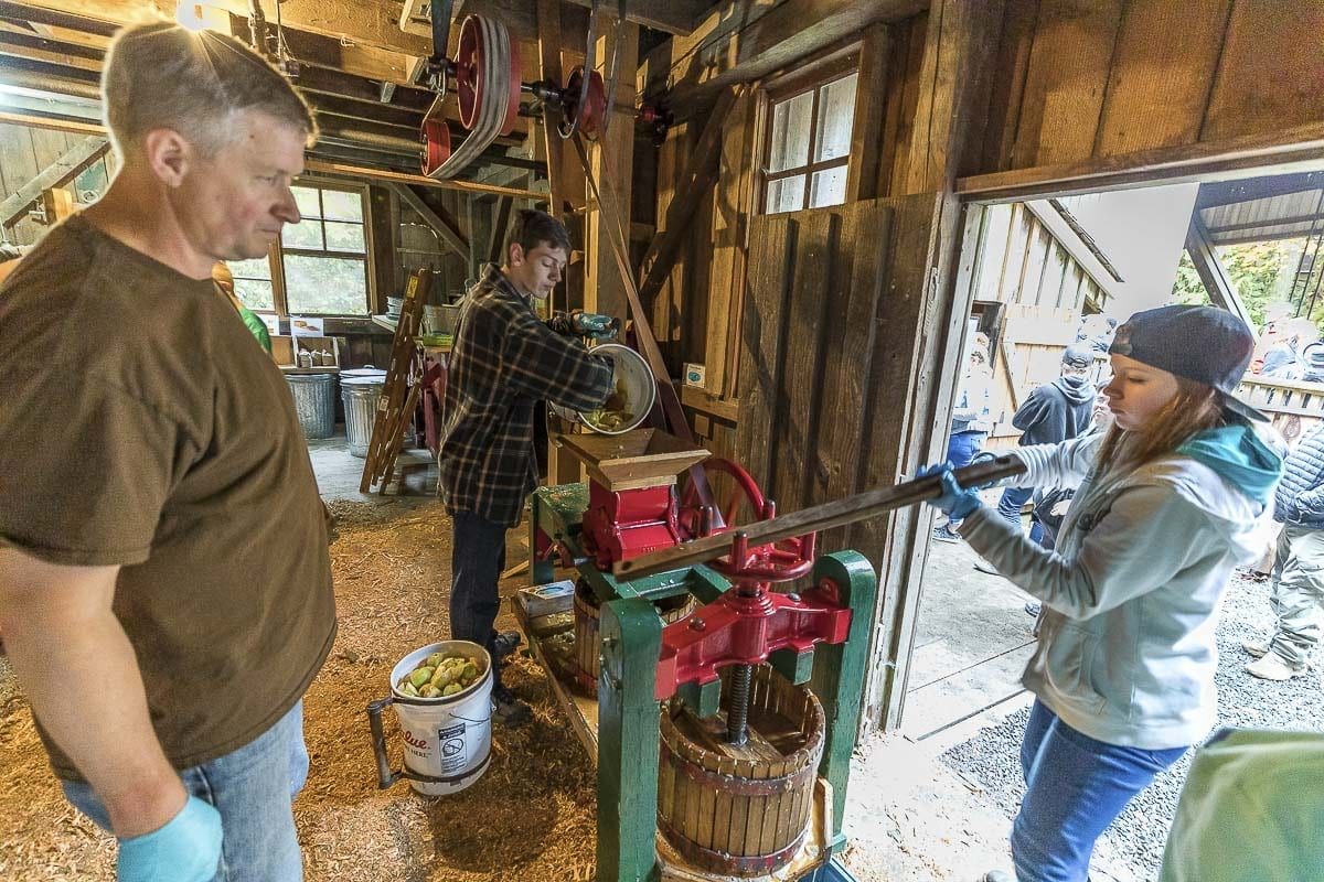 Volunteers Ken Clark and Zachary Morrison help Riley Shirley operate an old style cider press at the Cedar Creek Grist Mill. Photo by Mike Schultz