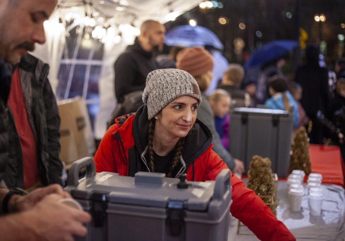 Darci Andrews from City Harvest Church, serves people hot apple cider during one of the many rainy deluges at the Vancouver tree lighting on Black Friday. Photo by Jacob Granneman