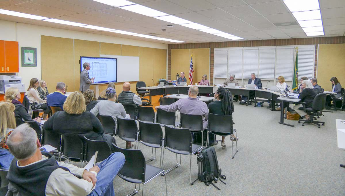 The Battle Ground School Board listens as Deputy Superintendent Denny Waters walks through updated boundary proposals to deal with overcrowding in the district. Photo by Chris Brown
