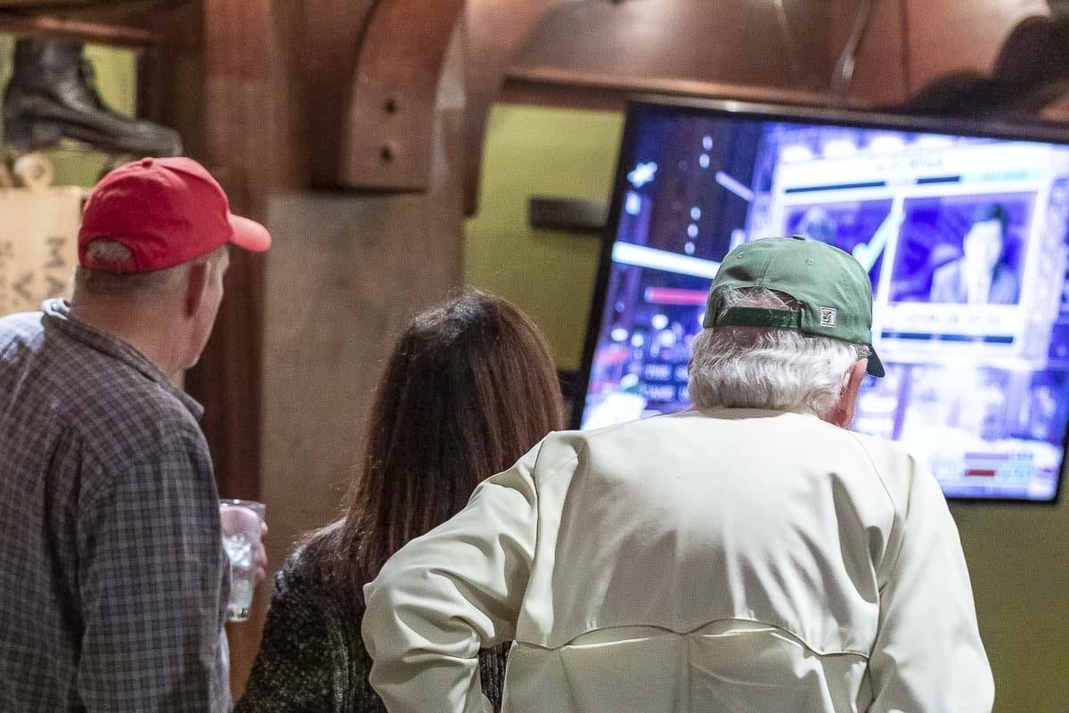 Attendees at Warehouse 23 on election night check results on a television. Photo by Mike Schultz