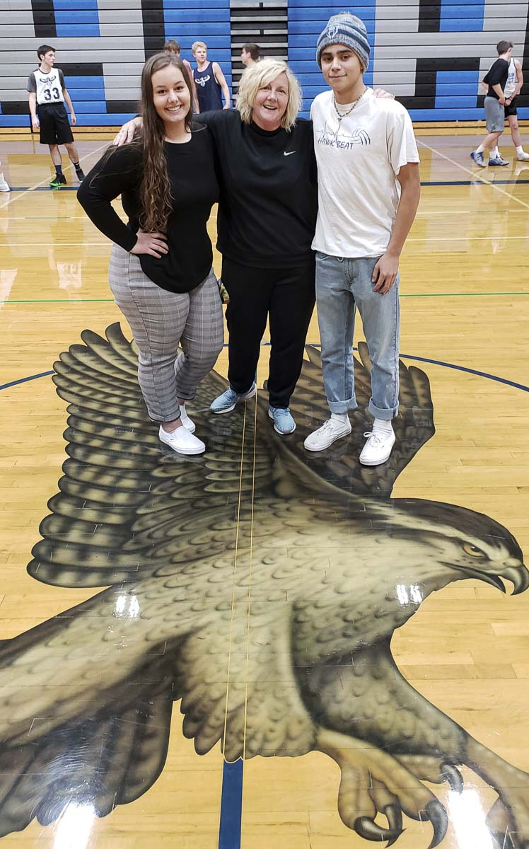 Brandi Webb (left) and Stephen Weinmuller (right) hang with Beth Tugaw, Hockinson's athletic coordinator and leadership advisor, at school this week. Weinmuller is a senior spirit leader, preparing to lead the student section in chants for one final football game this week. Webb, a junior, says she has a natural gift of being loud. Photo by Paul Valencia