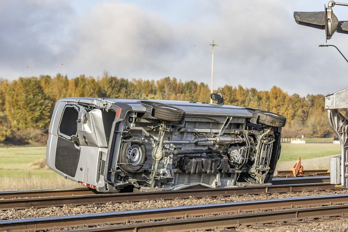A van being carried by a semi-truck ended up on railroad tracks after the truck was hit by a train in Ridgefield on Tuesday. Photo by Mike Schultz