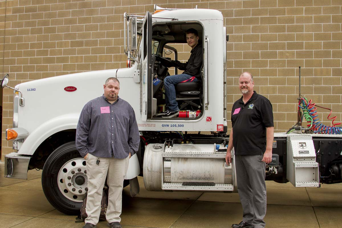 Tribeca Transport's Brad Cushman (truck driver, left) and Eric Thwaites (chief operating officer, right) show Shaun Sadlier (student, center) some of the features of one of their tractor trailers at the Woodland Days Career Fair. Photo courtesy of Woodland Public Schools