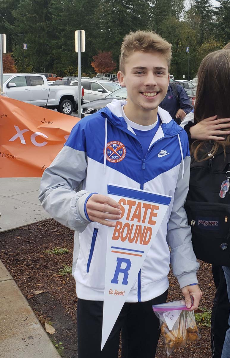 """Kyle Radosevich shows off his """"state bound"""" Ridgefield pennant that he and the rest of the school's cross country athletes received Friday morning. Photo by Paul Valencia"""