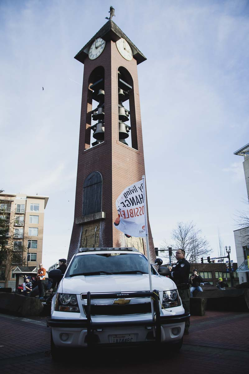 "Officer Jason Granneman of the Clark County Sheriff's Office, (CCSO), waits below the Vancouver clock tower for the flash mob to begin while also preparing to fly a CCSO drone to film the event. CCSO has a partnership program with Life Vest Inside, issuing ""kindness citations"" in the community. Photo by Alex McFeron"