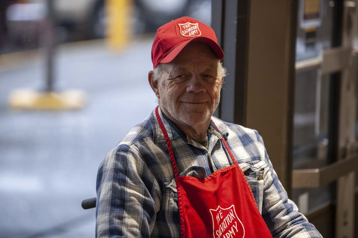 "Donald Schwartz rings the bell for the Salvation Army station in the front entrance of the Mill Plain Fred Meyer. As they pass, every customer receives a cordial, ""Merry Christmas!"" whether they stop to give or not. Photo by Jacob Granneman"