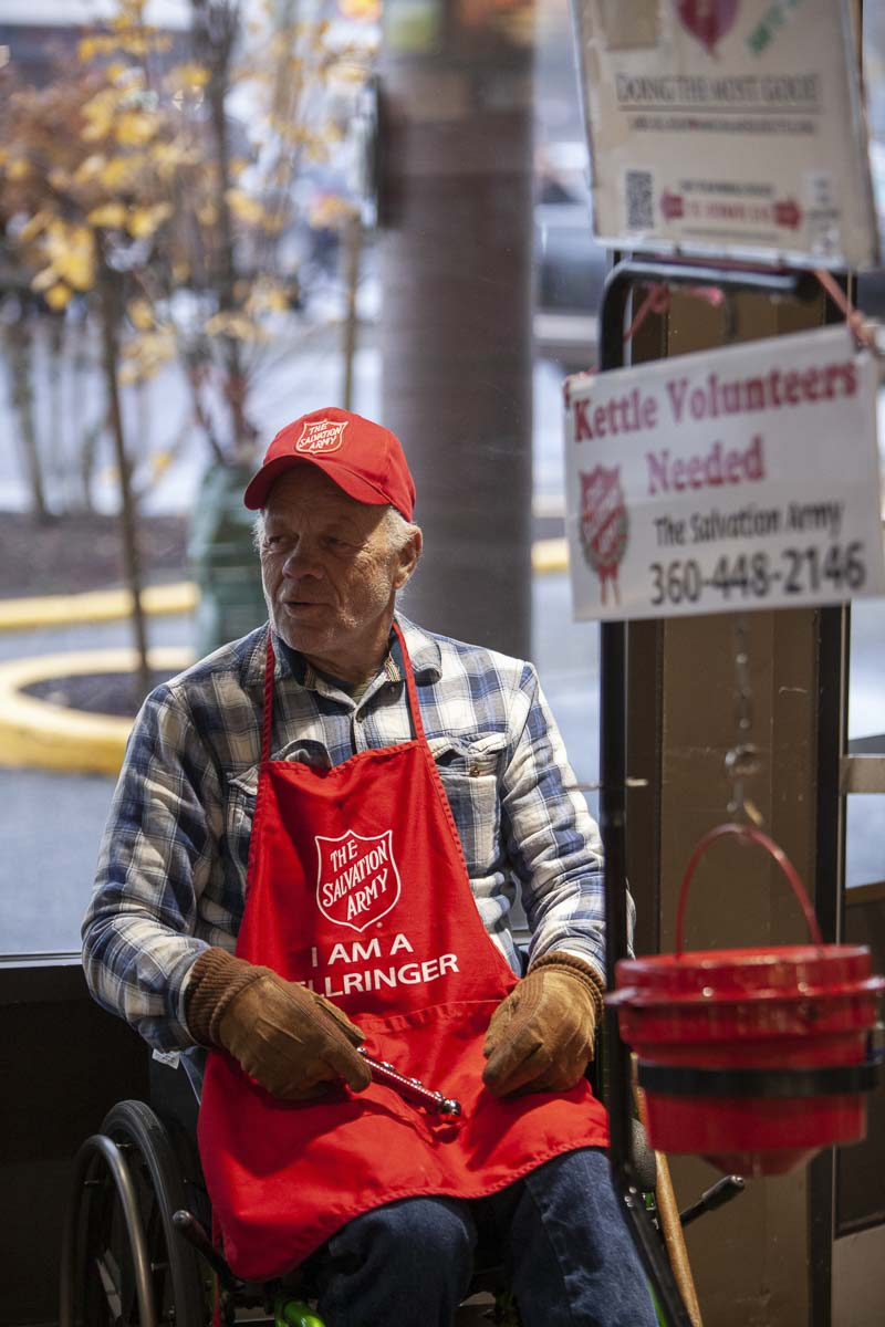 Salvation Army bell ringer, Donald Schwartz, sits smiling right inside the Fred Meyer off Chkalov and Mill Plain on a rainy afternoon before Thanksgiving. Photo by Jacob Granneman