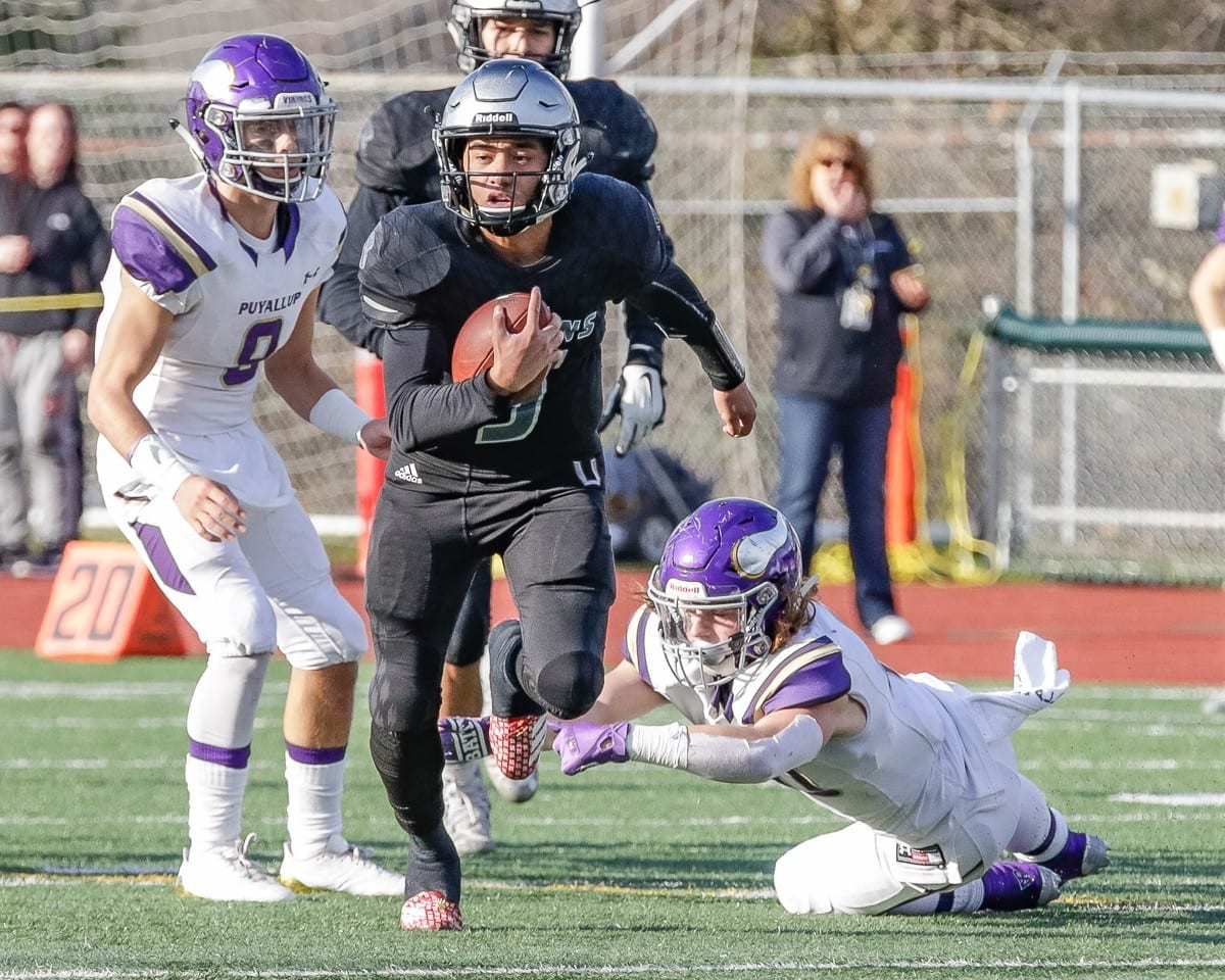 Union quarterback Lincoln Victor (5) breaks away from a pair of Puyallup defenders Saturday. Victor scored the game-winning touchdown with 2:52 left to play to lead the Titans to a 35-28 win in the Class 4A state semifinals at McKenzie Stadium. Photo by Mike Schultz