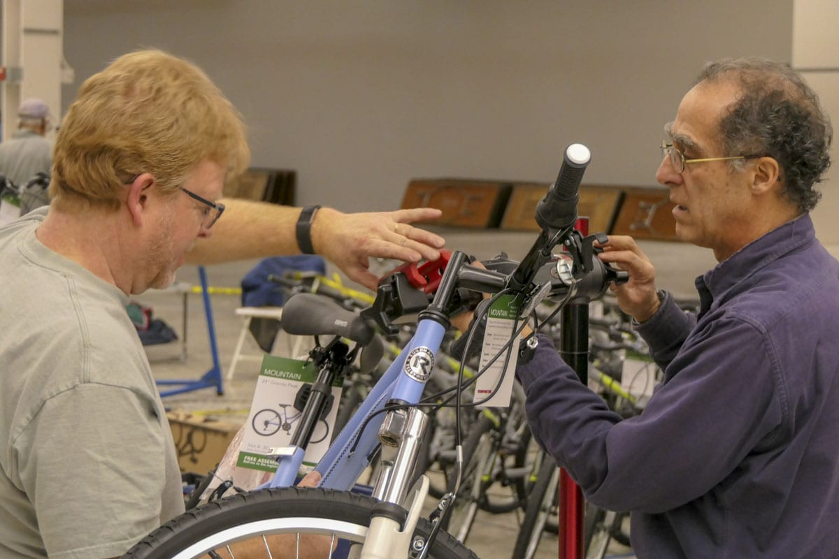 Volunteers Terry Toland and Peter Fels examine a bike to make sure it's safe at the annual Scott Campbell Christmas Promise bike build. Photo by Chris Brown