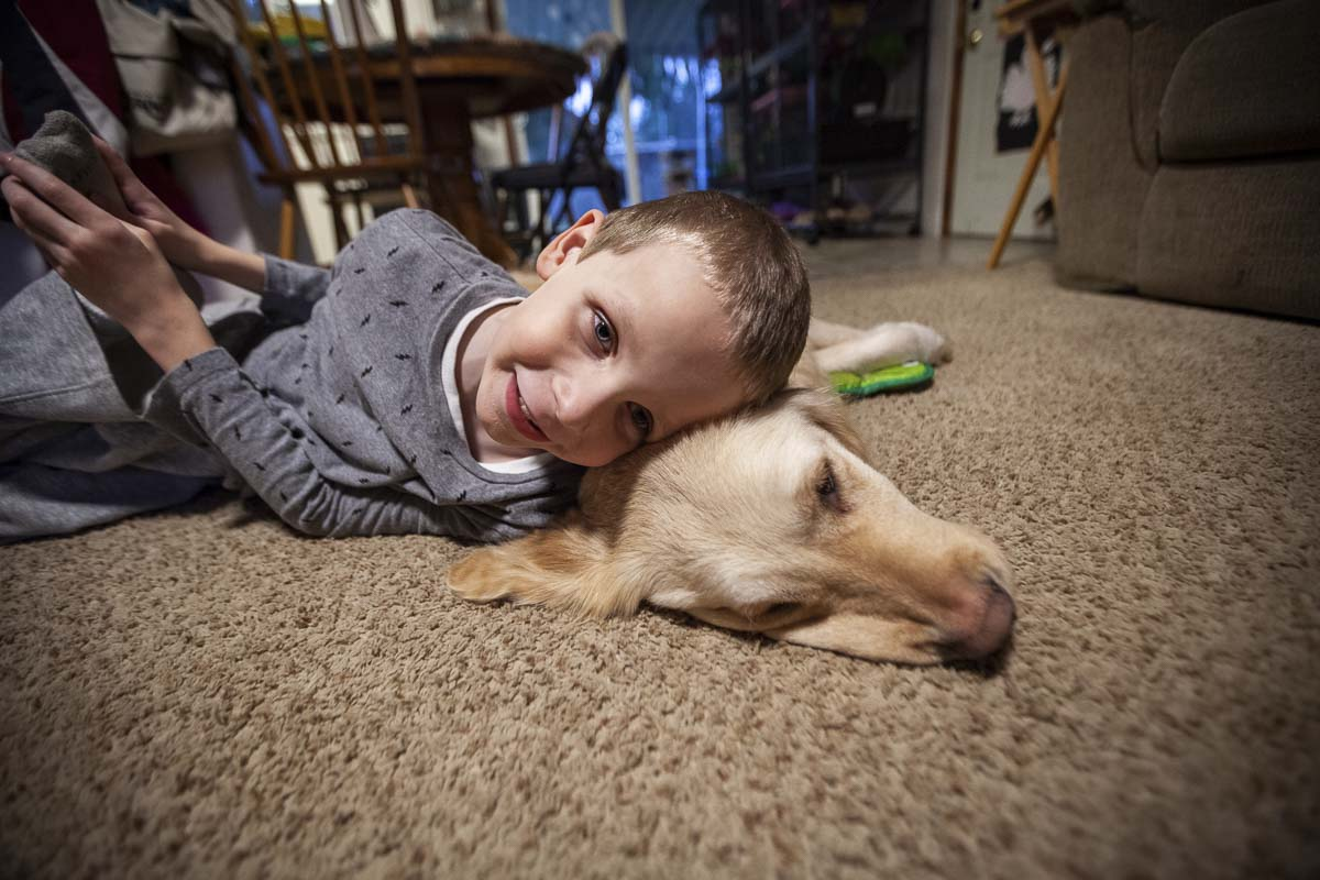 Cole Fish and his K9 Buddy, Jolene or Jojo, snuggle on the floor of the home in Vancouver. Cole got Jojo about a year ago because of he was having trouble sleeping. Blindness often causes strange dreams and difficulty staying asleep. Photo by Jacob Granneman